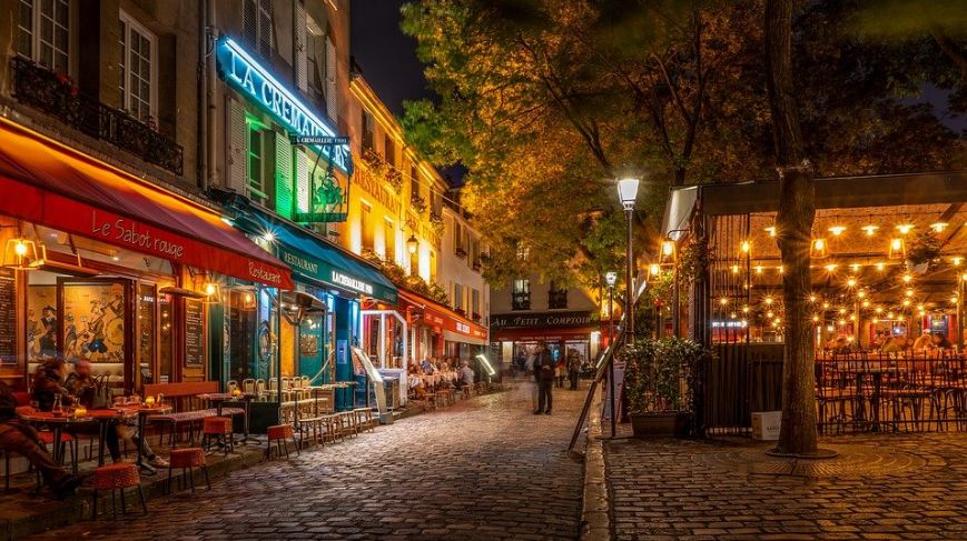 different French cafes and restaurants, tall green trees, yellow lights and bright streetlights