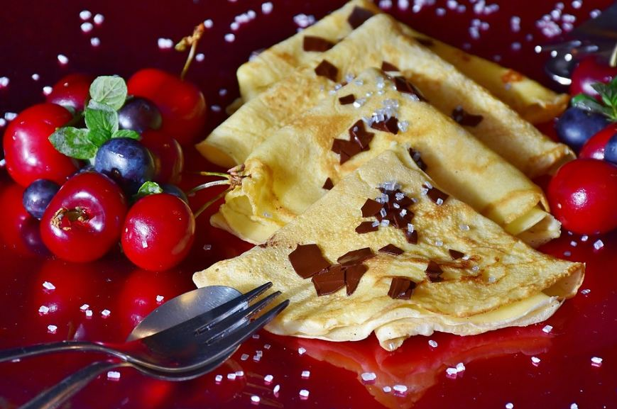 four pieces of crepe, cherries and blueberries, silver spoon and fork